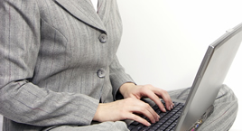 torso of woman with her hands on a laptop keyboard